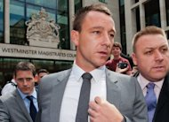 Chelsea captain John Terry (C) leaves Westminster Magistrates court in London on July 13. Football Association chiefs have been urged to follow the precedent set by the Luis Suarez case and take action against Terry for using racially offensive language