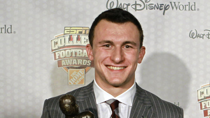 Texas A&M quarterback Johnny Manziel  displays his trophy for the Davey O'Brien Award after being named the nation's best quarterback at the Home Depot College Football Awards in Lake Buena Vista, Fla., Thursday, Dec. 6, 2012. (AP Photo/John Raoux)