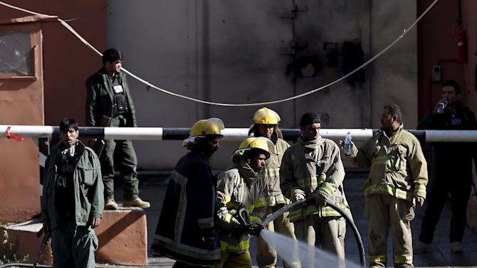Afghan firefighters spray water to wash the site of an attack in Kabul