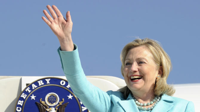 FILE - In this June 10, 2011 file photo, Secretary of State Hillary Rodham Clinton waves as the arrives at Lusaka International Airport in Lusaka, Zambia. If diplomatic achievements were measured by the number of countries visited, Hillary Rodham Clinton would be the most accomplished secretary of state in history. Since becoming secretary of state in 2009, Clinton has logged 351 days on the road, traveled to 102 countries and flown a whopping 843,839 miles, according to the State Department. (AP Photo/Susan Walsh, Pool)