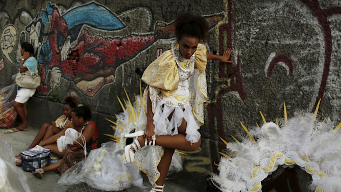 A reveller gets ready before the first night of the Carnival parade of samba schools in Rio de Janeiro's Sambadrome