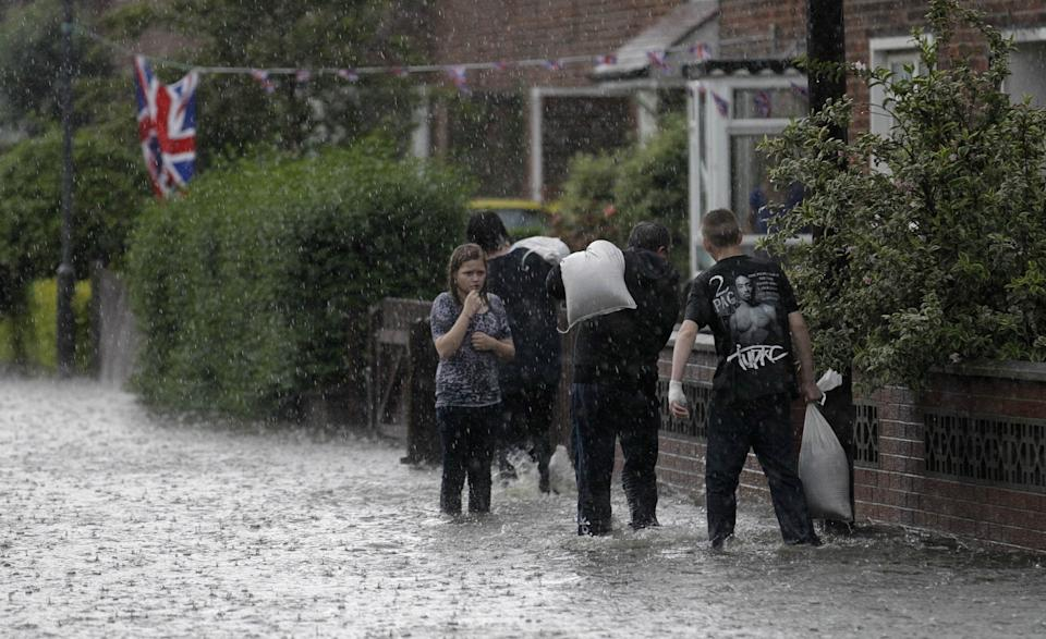Residents carry sandbags during heavy rainfall in the Cregagh estate in East Belfast, Northern Ireland, Wednesday, June 27, 2012. (AP Photo/Peter Morrison)