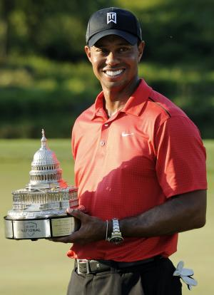 Tiger Woods poses with the trophy on the 18th green after winning the AT&T National golf tournament at Congressional Country Club in Bethesda, Md., Sunday, July 1, 2012. (AP Photo/Nick Wass)