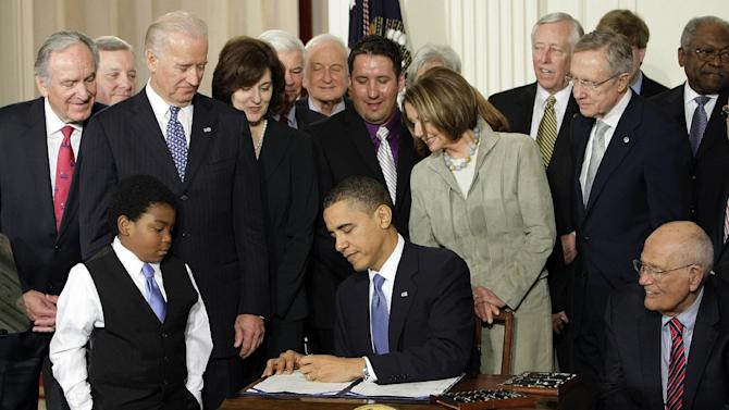 FILE - In this March 23, 2010 file photo, Marcelas Owens of Seattle, left, Rep. John Dingell, D-Mich., right, and others, look on as President Barack Obama signs the health care bill in the East Room of the White House in Washington. Medical claims costs _ the biggest driver of health insurance premiums _ will jump an average 32 percent for individual policies under President Barack Obama's overhaul, according to a study by the nation's leading group of financial risk analysts. Recently released to its members, the report from the Society of Actuaries could turn into a big headache for the Obama administration at a time when many parts of the country remain skeptical about the Affordable Care Act.  (AP Photo/J. Scott Applewhite, File)