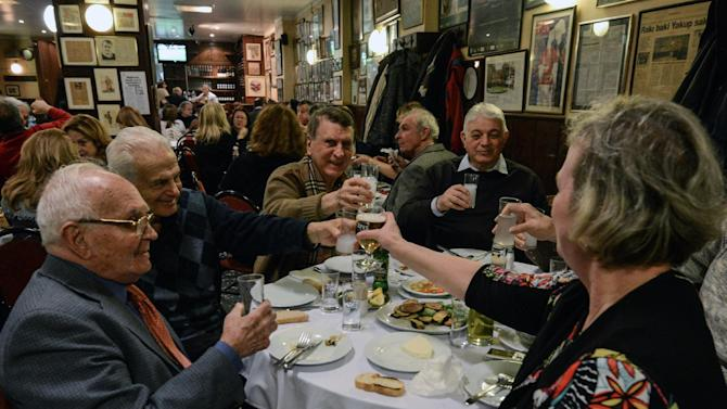 FILE - In this March 16, 2013 file photo, people toast with beer and raki, a traditional Turkish aniseed-based alcoholic drink, at an Istanbul restaurant, Turkey. A look at legislation passed in Turkey's parliament early Friday May 24 2013 that would ban all alcohol advertising and tighten restrictions on the sale of such beverages, and how such a law could affect tourists and liquor companies in the mainly Muslim but secular country.(AP Photo/File)