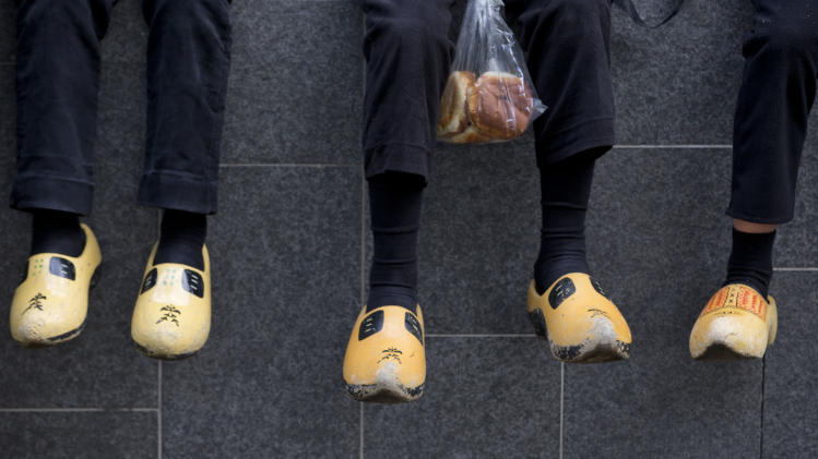 Boys from the village of Staphorst wearing traditional suits and wooden shoes, one clutching a plastic bag with sandwiches, pause to eat breakfast on their way to attend celebrations marking the official opening of the new parliamentary year with a speech outlining the government's plan and budget policies for the year ahead in The Hague, Netherlands, Tuesday, Sept. 17, 2013. (AP Photo/Peter Dejong)