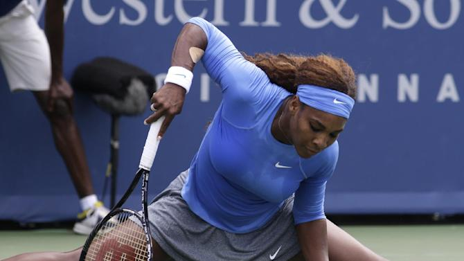 Serena Williams helps herself up after slipping against Victoria Azarenka, from Belarus, during the finals match at the Western & Southern Open tennis tournament, Sunday, Aug. 18, 2013, in Mason, Ohio. (AP Photo/Al Behrman)