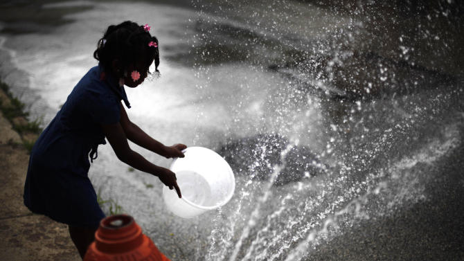 FILE - In this July 18, 2012 file photo, Jazia Pratt, 8, fills a bucket with water from a fire hydrant in the afternoon summer heat in Philadelphia.   Federal scientists say July was the hottest month ever recorded in the Lower 48 states, breaking a record set during the Dust Bowl of the 1930s. The average temperature last month was 77.6 degrees. That breaks the old record from July 1936 by 0.2 degree, according to the National Oceanic and Atmospheric Administration. Records go back to 1895. (AP Photo/Matt Rourke)