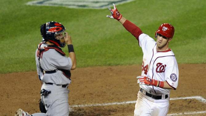 Washington Nationals' Bryce Harper, right, reacts after crossing home plate on a solo home run, next to St. Louis Cardinals catcher Yadier Molina in the third inning of Game 5 of the National League division baseball series on Friday, Oct. 12, 2012, in Washington. (AP Photo/Nick Wass)
