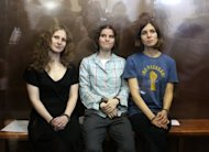 "Members of the all-girl punk band ""Pussy Riot"" Nadezhda Tolokonnikova (right), Maria Alyokhina (left) and Yekaterina Samutsevich sit in a glass-walled cage after being sentenced in Moscow on August 17. They were sentenced to two years in prison for performing a ""punk prayer"" in Moscow's main cathedral, in a trial called a farce by lawyers"