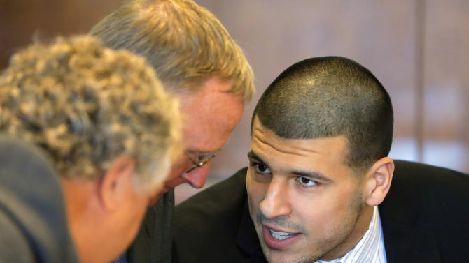 Former New England Patriots NFL football player Aaron Hernandez, right, confers with defense attorneys Michael Fee, left, and Charles Rankin during a pretrial court hearing in Fall River, Mass. on Wednesday, Oct. 9, 2013. Hernandez was indicted in August in the killing of 27-year-old Odin Lloyd, a semi-professional football player from Boston who was dating the sister of Hernandez's girlfriend. He has pleaded not guilty. (AP Photo/Brian Snyder, Pool)