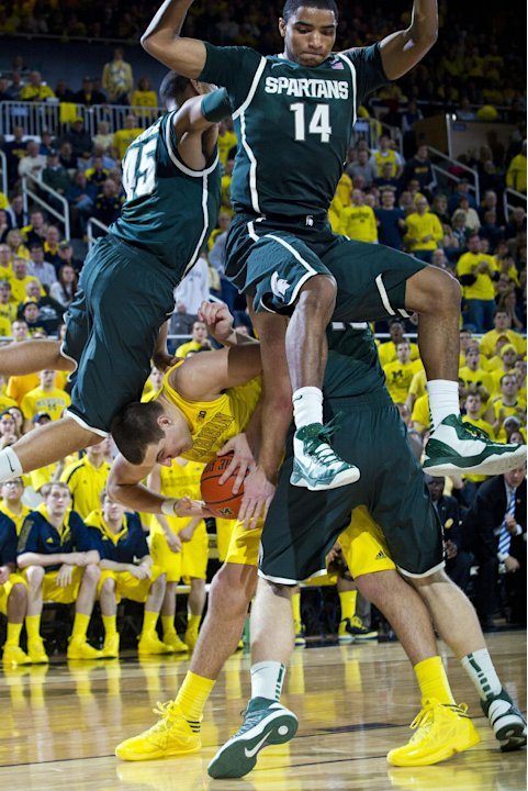 Michigan forward Mitch McGary, bottom, ducks under Michigan State guards Denzel Valentine (45) and Gary Harris (14), in the second half of an NCAA college basketball game on Sunday, March 3, 2013, at
