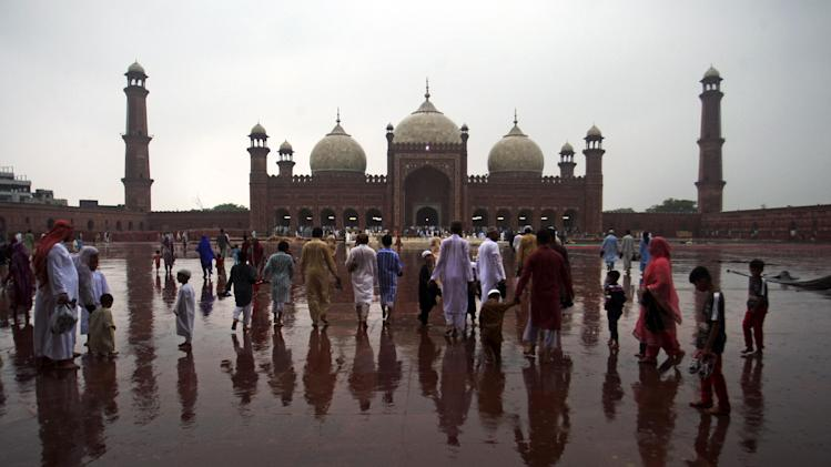 Pakistani Muslims walk towards the Badshahi mosque to offer the Eid al-Fitr prayer at the beginning of a major holiday marking the end of the fasting month of Ramadan in Karachi, Pakistan, Tuesday, July 29, 2014. Millions of Muslims across the world are celebrating the Eid. (K.M. Chaudary)