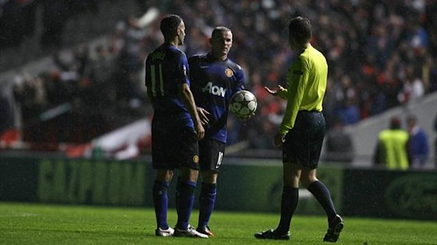 Referee Felix Brych of Germany (R) speaks to Manchester United's Wayne Rooney (C) and Ryan Giggs as their Champions League Group H soccer match against Braga is stopped due to an electrical failure at the Municipal stadium