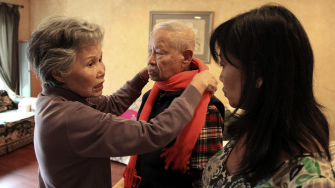 Shou-Mei Li, left, wraps a scarf around her husband Hsien-Wen Li, who is an Alzheimer's patient, as their daughter Shirley Rexrode, right, looks on, at their home in San Francisco, in this photo taken Thursday, Sept. 1, 2011.  Dementia is poised to become a defining disease of a rapidly aging population _ and a budget-busting one for Medicare, Medicaid and families. The Obama administration is developing the first national Alzheimer's plan to combine research aimed at fighting dementia with help for caregivers. Around the country, thousands of families are pleading for changes to improve early diagnosis and help keep loved ones at home instead of in nursing homes.  (AP Photo/Ben Margot)