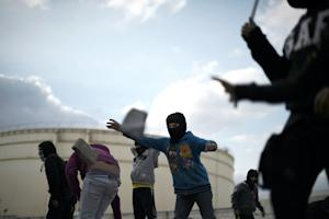 Bahraini protesters collect stones during clashes with…