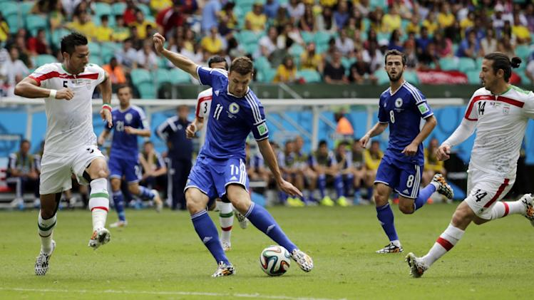 Bosnia's Edin Dzeko, center, scores the opening goal during a group F World Cup soccer match between Bosnia and Iran at the Arena Fonte Nova in Salvador, Brazil, Wednesday, June 25, 2014