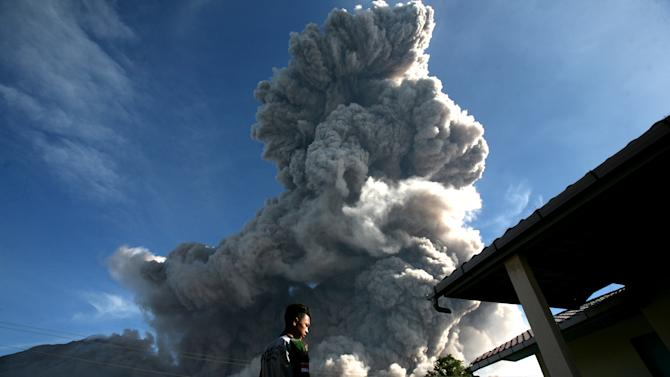 In this Thursday, June 25, 2015, file photo, a man watches as Mount Sinabung releases volcanic material into the air in Tiga Serangkai, North Sumatra, Indonesia. The volcano has spewed hot lava almost daily since its alert status was raised early this month to the highest level. Thousands of villagers whose homes are in the danger zone have been evacuated to safer areas. (AP Photo/Binsar Bakkara)