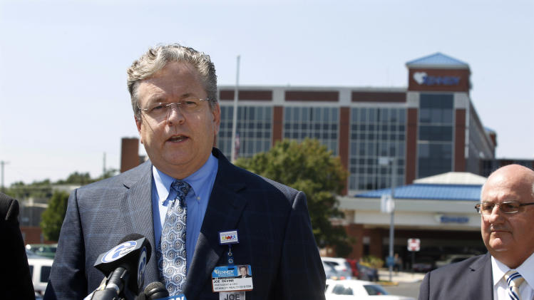 Joe Devine, left, with Kennedy Health System stands in front of Kennedy Hospital as he answers a question about shootings at the facility Wednesday, Aug. 27, 2014, in Stratford, N.J. Authorities say Raymond Wychowanec fatally shot his hospitalized wife, Denise, tried to kill himself, and a body was found later at the couple's home. Authorities are investigating what ties the hospital homicide may have with the death of a person found a short time later in the family's home in Glendora in southern New Jersey. (AP Photo/Mel Evans)