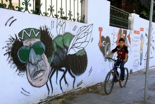 A Libyan boy cycles past graffiti depicting former strongman Moamer Kadhafi painted on a wall in Tripoli, 2011. Political campaigning for a national assembly begins on Monday, a milestone in Libya's troubled path to democratic elections after four decades of dictatorship under Kadhafi