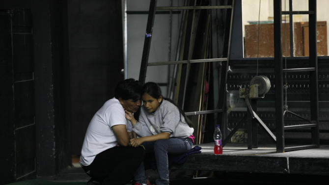 """In this Sept. 21, 2012 photo, singer Jennyfer Avila, experiencing a bout of stage fright, is comforted by her father prior to her performance in """"Suenos,"""" or """"Dreams,"""" one of Ecuador's most successful musicals, at the Casa de la Cultura theater in Quito, Ecuador. The musical is based in part on the dreams of young people with disabilities and is presented by the nonprofit foundation El Triangulo. (AP Photo/Dolores Ochoa)"""