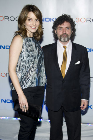"FILE - This Dec. 20, 2012 file photo shows Tina Fey, left, and her husband Jeff Richmond at the ""30 Rock"" farewell wrap party in New York. After seven seasons, ""30 Rock"" airs its series conclusion Thursday at 8 p.m. EST on NBC. Fey serves as star, writer and creator of the series and Richmond is executive producer and the composer and arranger for the show. (Photo by Charles Sykes/Invision/AP, file)"
