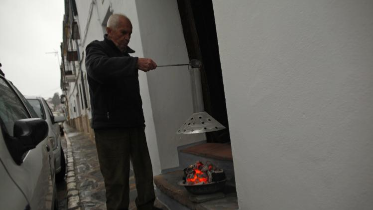 Diego checks a coal brazier at the entrance of his house on a cold winter's day in Ronda