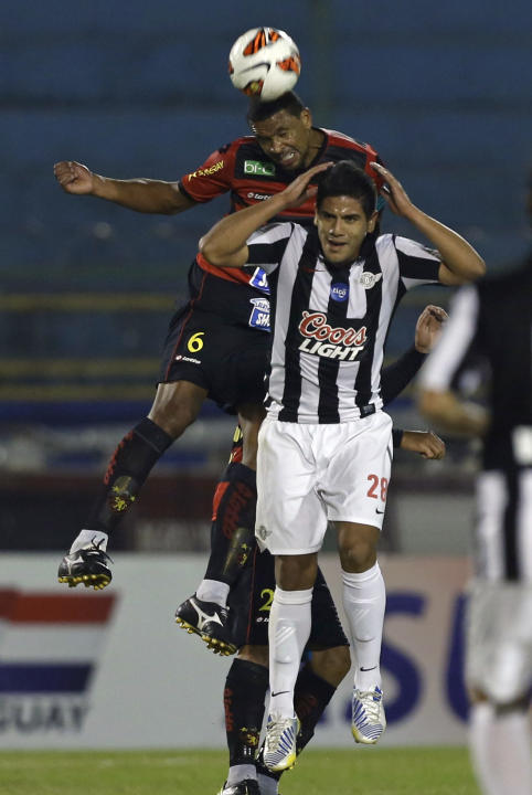 Pereira of Brazil's Sport Recife, behind, fights for the ball with Jose Recalde, of Paraguay's Libertad, at a Copa Sudamericana soccer game in Asuncion, Paraguay, Wednesday, Sept. 25, 2013
