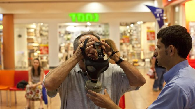 Israeli  Aviv Levy tries on a gas mask at a distribution center in a shopping mall in Mevaseret Zion near Jerusalem,   Wednesday, July 25, 2012. Israel's foreign minister warned on Wednesday his country will act immediately if it discovers Islamic militants are raiding Syria's chemical or biological weapons stocks, while Israelis rushed to stock up on gas masks as the bellicose rhetoric swells. (AP Photo/Sebastian Scheiner)