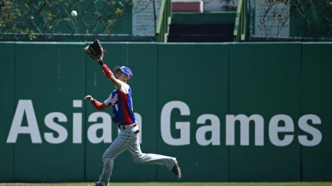 Hong Kong's center fielder Chiu Yan Nok Enroy catches a fly out from Taiwan's hitter Lin Han at the sixth inning during their preliminary round baseball game at the Munhak Baseball Stadium during the 17th Asian Games in Incheon