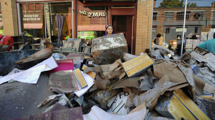 Meyru Bhanti, center, throws an unsalvageable item into an overflowing dumpster outside her parents' business two days after Tropical Storm Irene, in Brattleboro, Vt., Tuesday, Aug. 30, 2011.  (AP Photo/Jessica Hill)