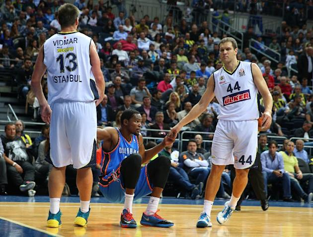 The NBA team Oklahoma City Thunder's Kevin Durant, center, is helped up by Gasper Vidmar and Bojan Bogdanovic of Fenerbahce Ulker during a preseason basketball game in Istanbul, Turkey, Saturday, Oct.