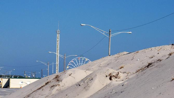 In this Feb. 15, 2013 photo, one of the well-established sand dunes in Seaside Park N.J., is shown that helped protect oceanfront homes during Superstorm Sandy, while its neighbor to the north, Seaside Heights, suffered catastrophic damage without dunes. Sandy showed how dunes protect homes along the coast, yet not all oceanfront property owners want them, fearing lost waterfront views and fearing that giving the government permission to build bigger dunes could lead to construction of boardwalks or amusements behind their pricey homes. (AP Photo/Wayne Parry)