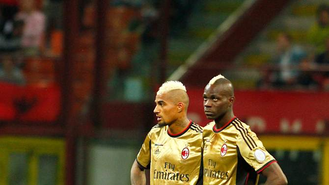 FILE - In this Sunday May 12, 2013, file photo, AC Milan players Kevin Prince Boateng, left, and Mario Balotelli look toward the stands during a stoppage in play in a Serie A soccer match between AC Milan and AS Roma, at Milan's San Siro Stadium.  The game was stopped for almost two minutes because of racial abuse by Roma fans towards Balotelli and Boateng. (AP Photo/Lapresse, Davide Spada, File) ITALY OUT