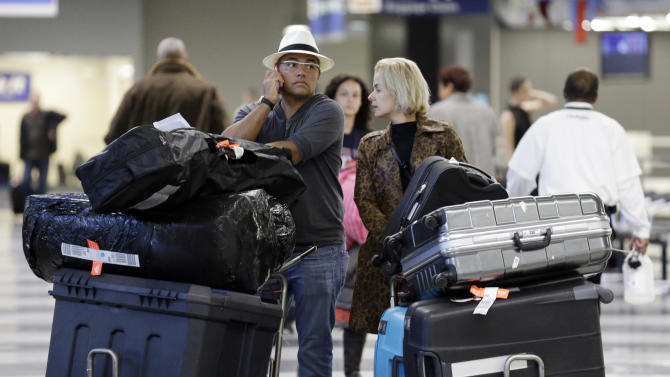 FILE - In this Dec. 1, 2013 file photo, travelers walk through terminal 3 baggage claim at O'Hare International airport in Chicago. The government reported Monday, May 5, 2014, that U.S. airlines raised $3.35 billion from bag fees in 2013, down 4 percent from 2012. That's the biggest decline since fees to check a bag or two took off in 2008. (AP Photo/Nam Y. Huh, File)
