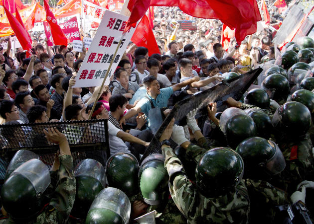 Chinese demonstrators clash with policemen at the barricades during an anti-Japan protests outside the Japanese Embassy in Beijing Saturday, Sept. 15, 2012. Angry protesters staged anti-Japanese demon