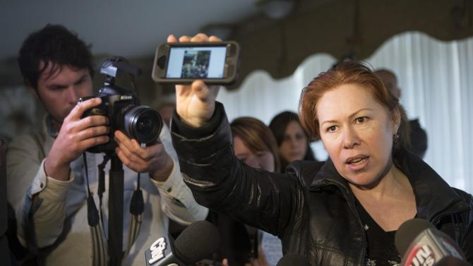 Maret Tsarnaeva, an aunt of the two suspects in the Boston Marathon bombing, holds a reporter's smart phone which displays a scene from the bomb site, as she speaks to journalists in the lobby of her apartment building in Toronto on Friday April 19, 2013.  Tamerlan Tsarnaev, a 26-year-old who had been known to the FBI as Suspect No. 1 and was seen in surveillance footage in a black baseball cap, was killed overnight, officials said. His brother, a 19-year-old college student who was dubbed Suspect No. 2 and was seen wearing a white, backward baseball cap in the images from Monday's deadly bombing at the marathon finish line, escaped. (AP Photo/The Canadian Press, Chris Young)