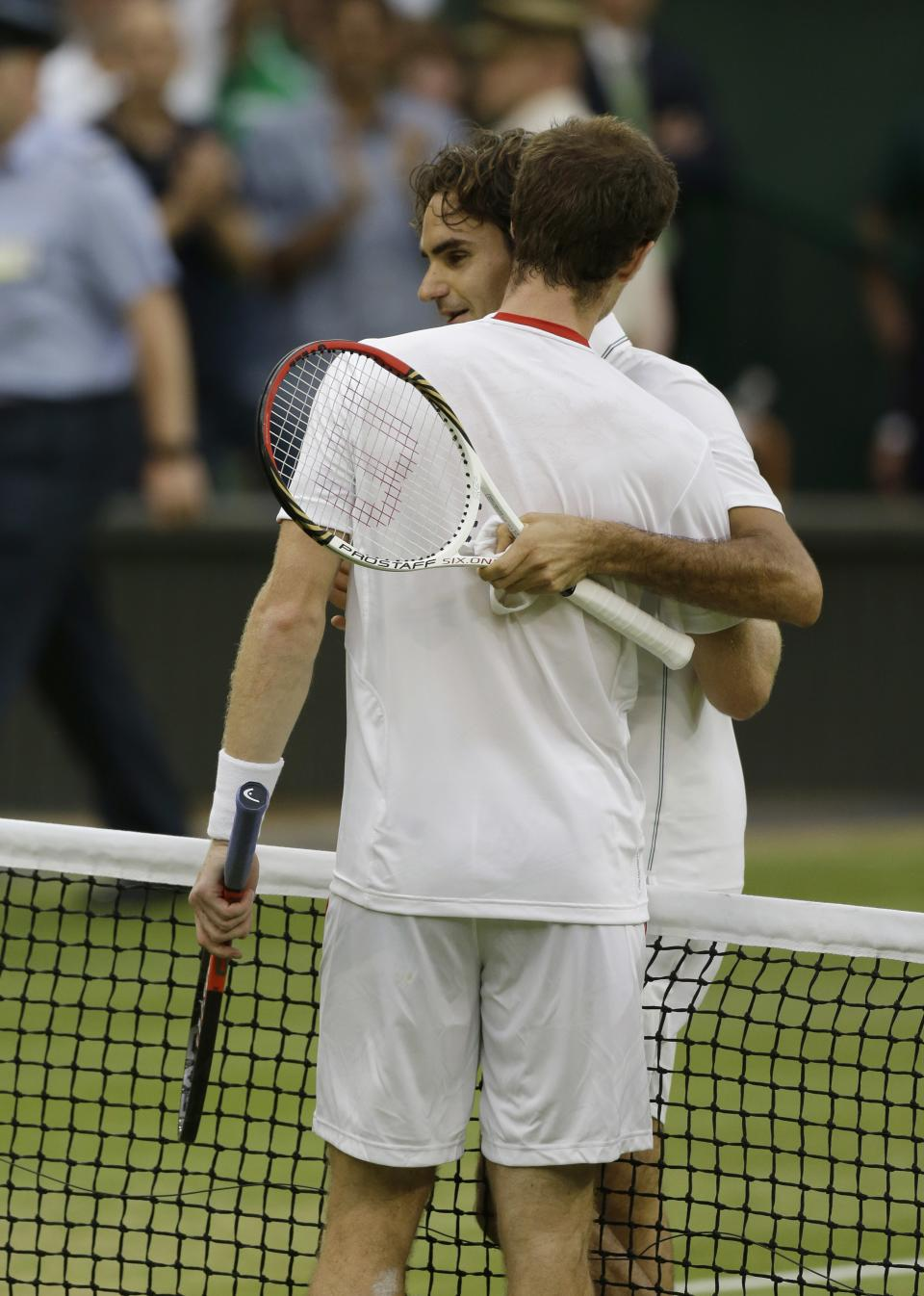 Roger Federer of Switzerland, back, is congratulated by Andy Murray of Britain after winning the men's singles final against  at the All England Lawn Tennis Championships at Wimbledon, England, Sunday, July 8, 2012. (AP Photo/Anja Niedringhaus)