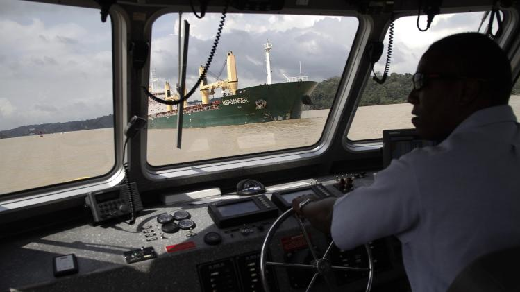 A pilot maneuvers a boat near a cargo ship in the Panama Canal in Gamboa near Panama City