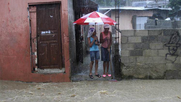 Women stand outside their home on a flooded street in the Cristo Redentor, or Christ Redeemer neighborhood, in Santo Domingo, Dominican Republic, Wednesday, July 10, 2013. Tropical Storm Chantal was downgraded Wednesday to a tropical wave as its scattered clouds drifted quickly westward toward Jamaica. But heavy rains from the weakened system continued to drench parts of Haiti and the Dominican Republic and force the evacuation of thousands from flood-prone areas. (AP Photo)