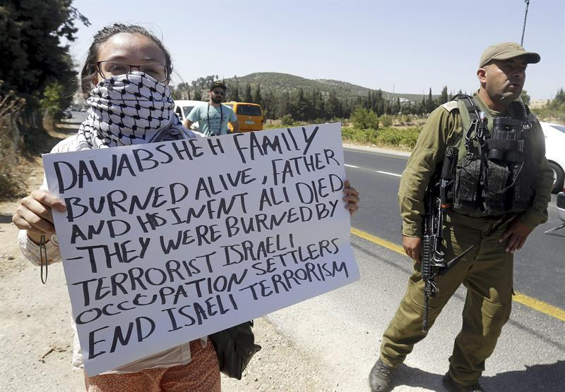 HEB02. Hebron (---), 08/08/2015.- A foreign activists holds a placard next to an Israeli security personnel during a protest on Route 60, near the West Bank city of Hebron, 08 August 2015, in solidarity with the Dawabsha family from the village of Douma, whose home was attacked by suspected Jewish extremists. The father of the Palestinian infant killed in firebomb attack by suspected Jewish extremist in the West Bank has died of his injuries at an Israeli hospital, Palestinians said on 08 August. Mosques in the village of Douma, south of the city of Nablus, announced the death of Saad Dawabsha, 37, on loudspeakers. His 18-month-old son Ali died in the arson attack on 31 July, his wife and son Ahmad, 4, are being treated for serious burns in Israel. (Atentado, Protestas) EFE/EPA/ABED AL HASHLAMONI