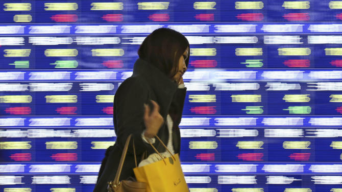 A woman walks by an electronic stock board of a securities firm in Tokyo, Tuesday, Dec. 17, 2013. Most Asian stock markets edged up Tuesday, with some indexes regaining slight losses after opening in directionless trading ahead of the U.S. Federal Reserve meeting. (AP Photo/Koji Sasahara)