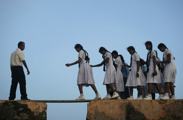 School girls walk across a plank on the walls of the 16th century Dutch fort in Galle