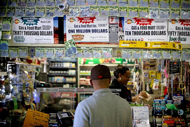 A customer waits for his lottery ticket to print out at a convenience store, Monday, Nov. 26, 2012, in Atlanta. As the Powerball jackpot soars, a Georgia Lottery official says the agency is working to