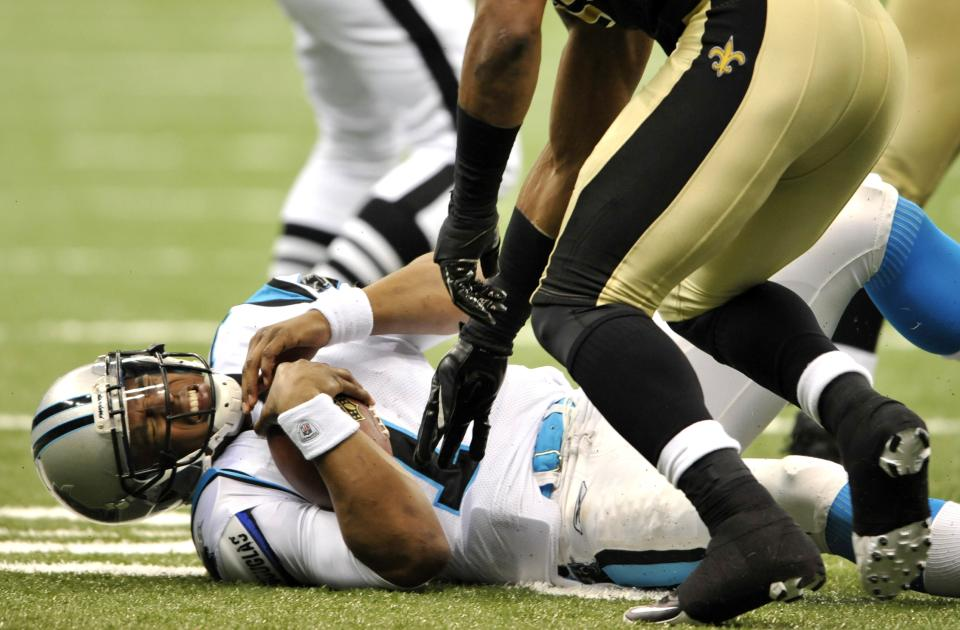 Carolina Panthers quarterback Cam Newton (1) grimaces on the turf after being sacked by New Orleans Saints outside linebacker Martez Wilson (95) during the third quarter of an NFL football game in New Orleans, Sunday, Jan. 1, 2012. (AP Photo/Bill Feig)