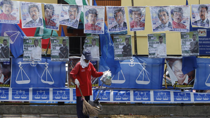 A worker cleans up a roadside in front of election campaign posters and flags of Malaysia's ruling National Front coalition ahead of the upcoming general elections in Kuala Lumpur, Malaysia, Monday, April 29, 2013. With less than a week to general elections, Malaysia's opposition alliance is banking on the promise of bold change to end the governing coalition's 56-year rule. It says a new economic playing field will strip away decades of race-based policies that it believes bred corruption and hampered growth. (AP Photo/Lai Seng Sin)