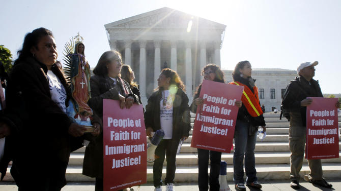 "Leonida Martinez, left, from Phoenix, Ariz., and others, take part in a demonstration in front of the Supreme Court in Washington, Wednesday, April 25, 2012, as the court questions Arizona's ""show me your papers"" immigration law . (AP Photo/Charles Dharapak)"