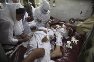 Pakistani hospital staff treat youths injured in an attack, at a local hospital in Peshawar, Pakistan on Tuesday, Sept 13, 2011. Gunmen attacked a school van in northwestern Pakistan killing three children, the driver and police said. (AP Photo/Mohammad Sajjad)
