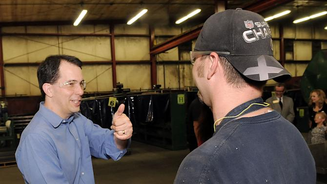 Wisconsin Gov. Scott Walker, left, shakes hands Monday, June 4, 2012, with J & D Manufacturing employee Ryan Schweikert of Eau Claire, Wis., during a tour of the Altoona, Wis., company.  Walker visited six of Wisconsin's largest cities on the day before the state's historic recall election.  (AP Photo/Eau Claire Leader-Telegram, Steve Kinderman)