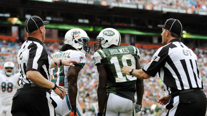 Miami Dolphins cornerback Richard Marshall (31) and New York Jets wide receiver Santonio Holmes (10) engage each other as head linesman Greg Maxwell (67) and another official attempt to restrain them during the second half of an NFL football game, Sunday, Sept. 23, 2012, in Miami. (AP Photo/Rhona Wise)